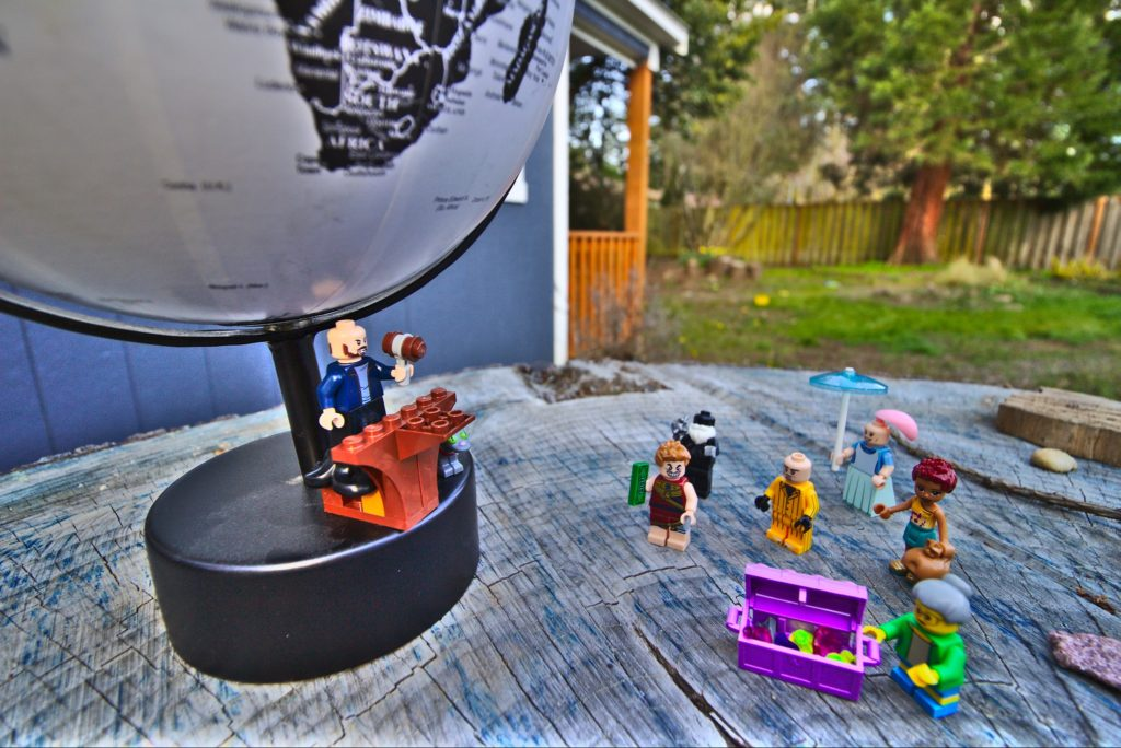 A lego man selling a globe to a few villinous looking lego characters.